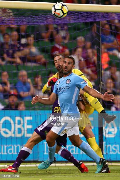 Emmanuel Muscat of Melbourne assists Dean Bouzanis in blocking a shot on goal during the round 15 ALeague match between the Perth Glory and Melbourne...