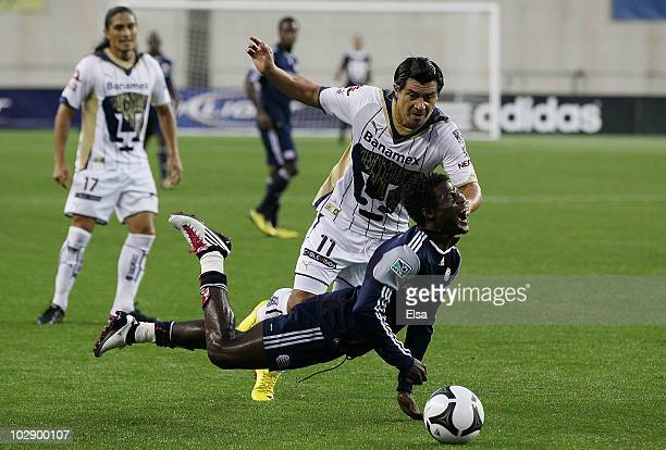 Emmanuel Osei of the New England Revolution is tripped up by Juan Carlos Cacho of Pumas UNAM at Gillette Stadium on July 14 2010 in Foxboro...
