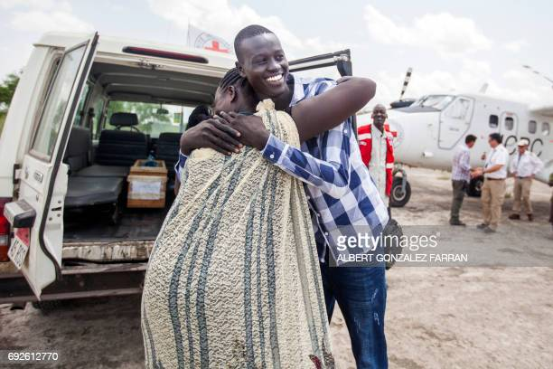 TOPSHOT Emmanuel Samuel 17 years old hugs his mother Georgina Pagan as he reunites with her after landing in Aburoc South Sudan on June 5 2017...