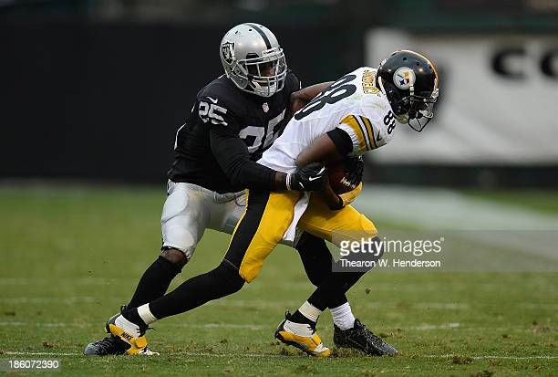 Emmanuel Sanders of the Pittsburgh Steelers gets wrapped up by DJ Hayden of the Oakland Raiders during the fourth quarter at O.co Coliseum on October...