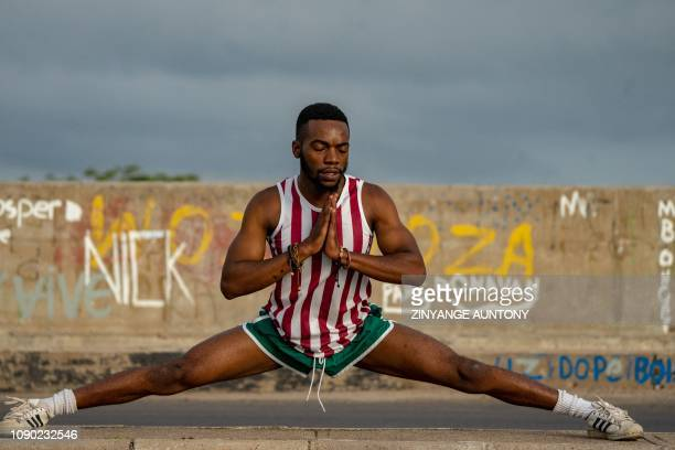 TOPSHOT Emmanuel Sibanda a 25yearold mechanical engineer does stretching exercises early in the morning on January 27 on the side of the road near...