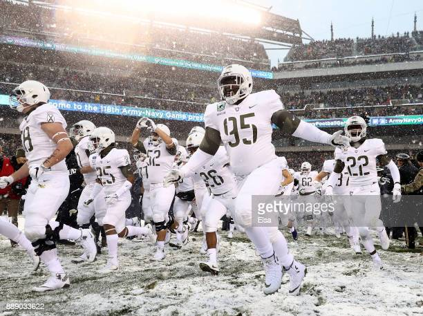 Emmanuel Ukhueligbe of the Army Black Knights and the rest of his teammates run out on the field before the game against the Navy Midshipmen on...