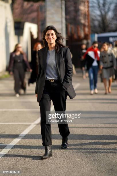 Emmanuelle Alt wears a black blazer jacket, a gray top, a belt, black pants, outside Alberta Ferretti, during Milan Fashion Week Fall/Winter...