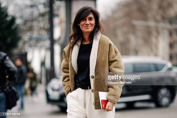 Emmanuelle Alt wears a black top a camel sheepskin jacket white pants outside Nina Ricci during Paris Fashion Week Womenswear Fall/Winter 2019/2020...