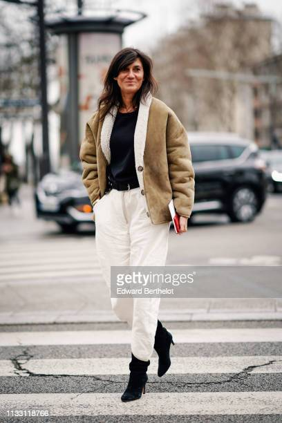 Emmanuelle Alt wears a black top a camel sheepskin jacket white pants black pointy high heeled boots outside Nina Ricci during Paris Fashion Week...