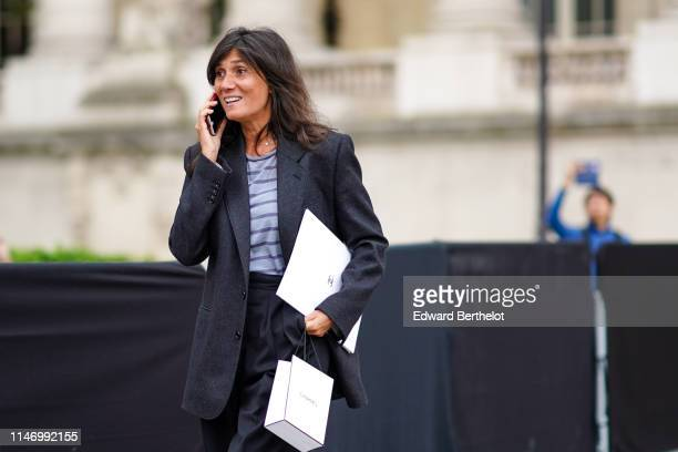 Emmanuelle Alt wears a dark grey jacket a blue and purple striped top black wide leg pants outside the Chanel Cruise Collection 2020 At Grand Palais...