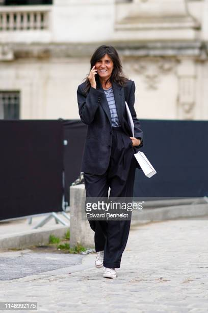 Emmanuelle Alt wears a dark grey jacket a blue and purple striped top black wide leg cuffed pants white sneakers outside the Chanel Cruise Collection...