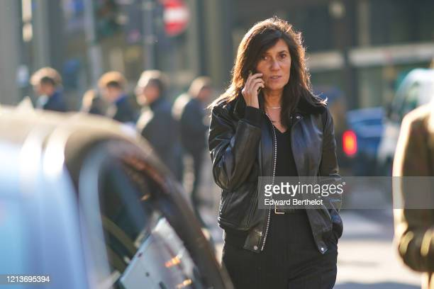 Emmanuelle Alt wears a necklace, a black leather bomber jacket, a black V-neck top, a black belt, black pants with thin white stripes, outside...