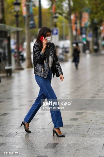 Emmanuelle Alt wears a white protective face mask a black leather shiny jacket blue flared denim jeans black pointy shoes outside Miu Miu during...