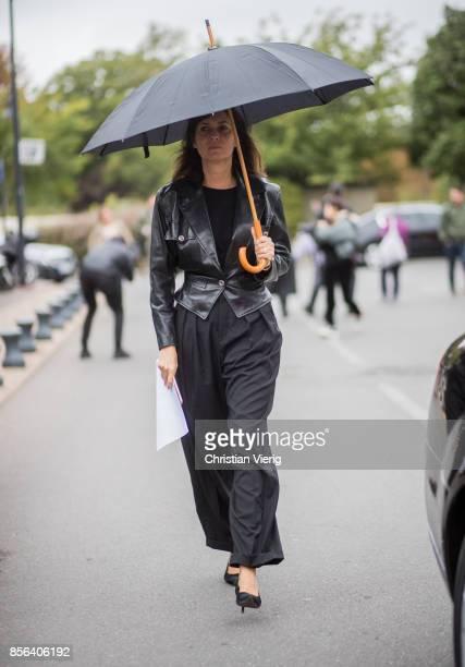 Emmanuelle Alt with an umbrella seen outside Balenciaga during Paris Fashion Week Spring/Summer 2018 on October 1 2017 in Paris France