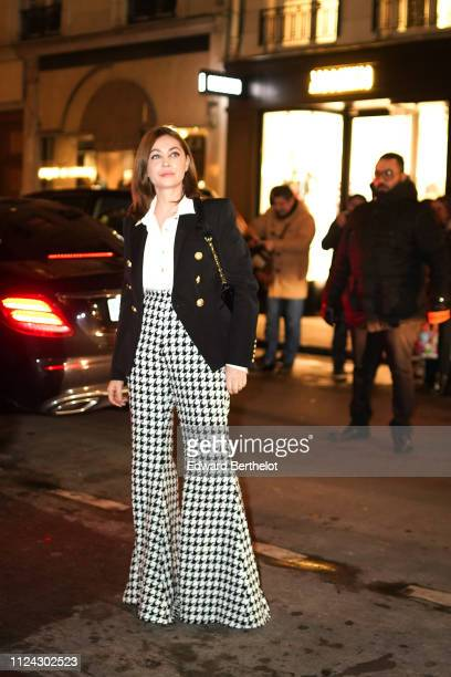 Emmanuelle Beart wears a blazer jacket with golden buttons a white shirt black and white flare pants outside Balmain during Paris Fashion Week Haute...