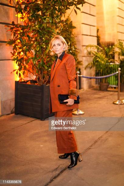 Emmanuelle Beart wears earrings a black shirt a rustcolor oversize doublebreasted jacket with fur cuffs rustcolor wide leg cuffed pants a black...