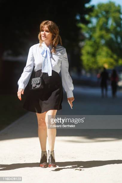 Emmanuelle Seigner wears a pale blue shirt, a Chanel bag, a black skirt, outside Alexandre Vauthier, during Paris Fashion Week -Haute Couture...