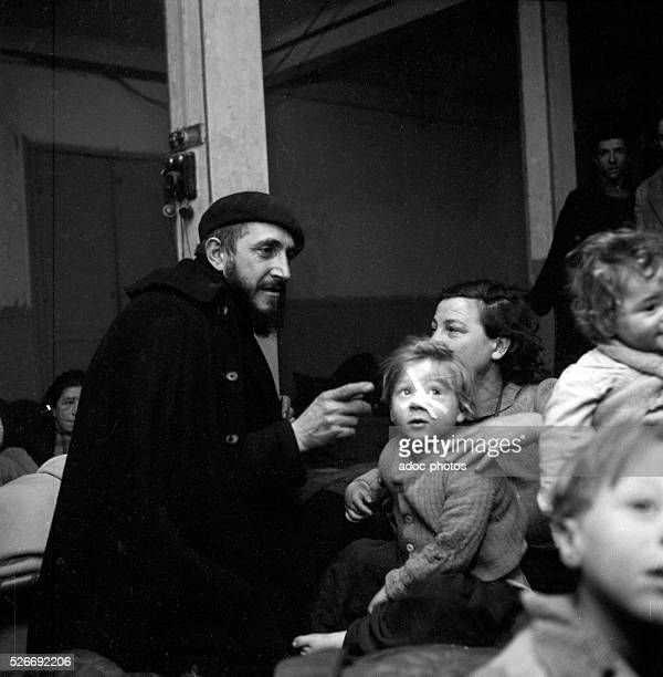 Emmaus movement Abb�� Pierre comforting a family In January 1954