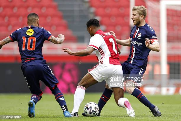 Emmen's Peruvian midfielder Sergio Pena and teammate Dutch forward Michael de Leeuw fight for the ball against Ajax's Dutch defender Jurrien Timber...