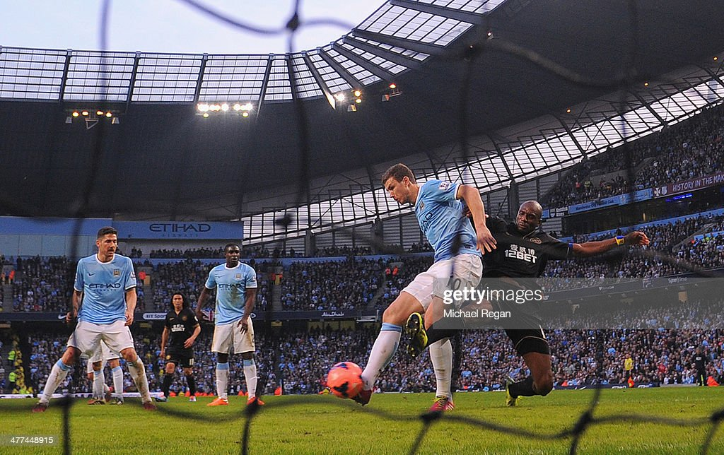 Emmerson Boyce of Wigan blocks a close range shot from Edin Dzeko of Manchester City during the FA Cup Quarter-Final match between Manchester City and Wigan Athletic at the Etihad Stadium on March 9, 2014 in Manchester, England.
