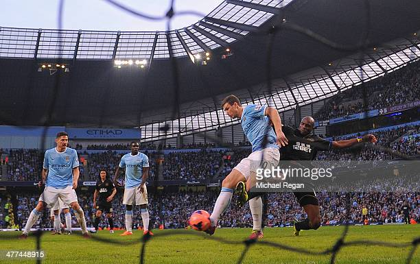Emmerson Boyce of Wigan blocks a close range shot from Edin Dzeko of Manchester City during the FA Cup QuarterFinal match between Manchester City and...