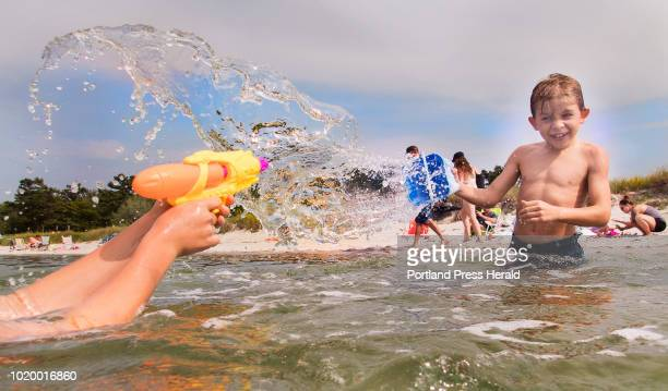 Emmet Johnson 8 of Portlandthrows a bucket of water at his brother James who is retaliating with a squirt gun while playing in the surf at Ferry...