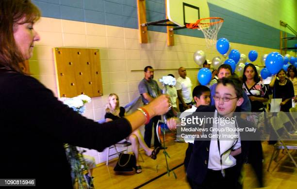 Emmet Torrance takes a flower from teacher Bev Sanders to give to his parents during the Continuation ceremony for the 5th grade class at Alicia...