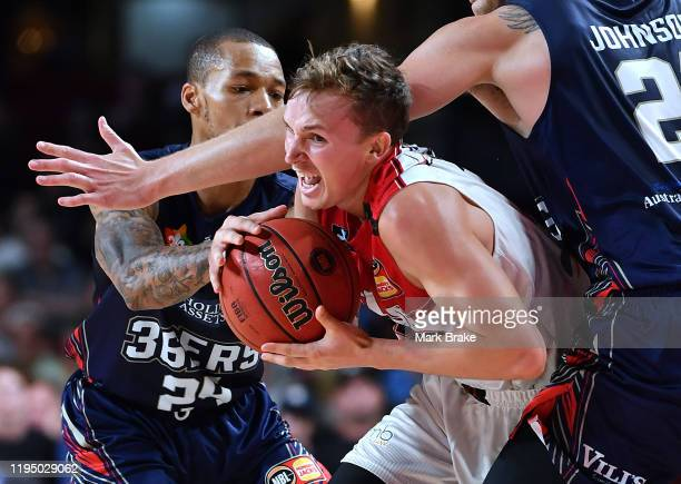Emmett Naar of the Hawks gets through Daniel Johnson of the 36ers and Jerome Randle of the 36ers during the round 12 NBL match between the Adelaide...