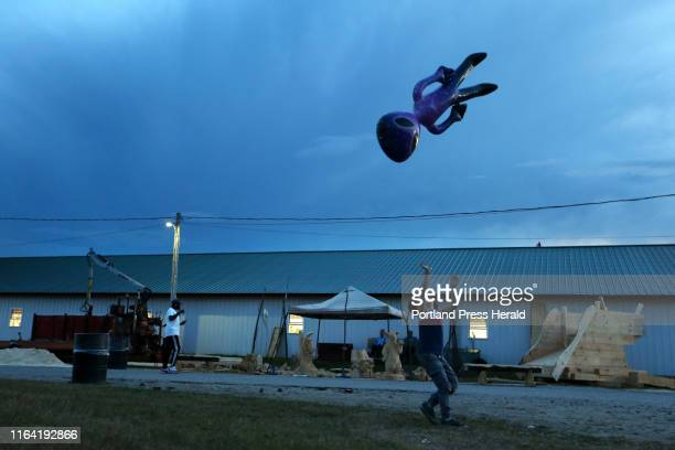 Emmett Stuart of Harpswell tosses an inflatable novelty alien into the air near a display of chainsaw carvings omg Friday at the Topsham Fair