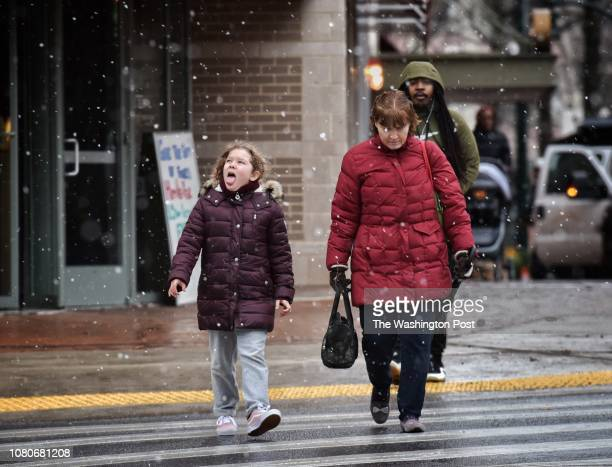 Emmi Horne tries to catch snowflakes on her toungue as she walks through downtown Silver Spring Maryland during a brief snow squall with her mom...