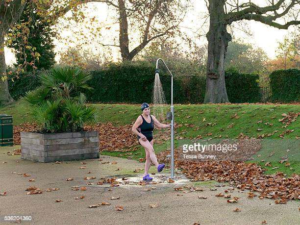 Emmi Hunte a member of the Serpentine Swimming Club takes a shower after swimming in the Serpentine Lake Hyde Park London UK The Serpentine Lake is...