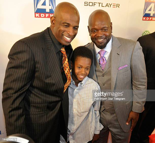 Emmitt Smith right and his son stop for a photo with Deion Sanders on the red carpet at the Dallas Cowboys 1992 Super Bowl team reunion at the Westin...