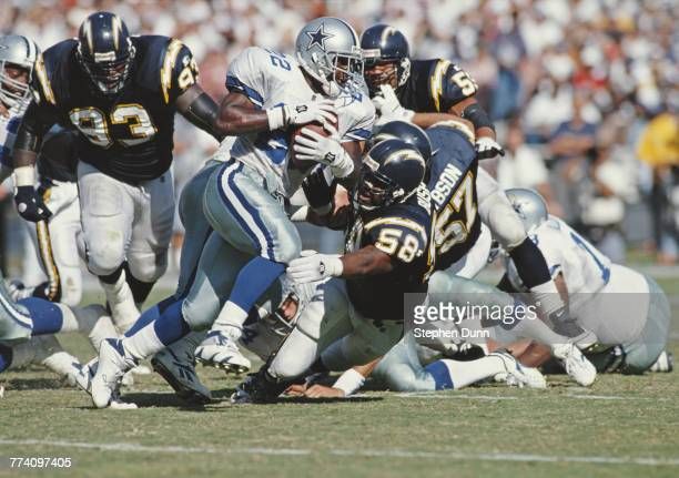Emmitt Smith, Running Back for the Dallas Cowboys runs the ball as Lewis Bush of the San Diego Chargers attempts to tackle him during their American...