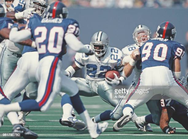 Emmitt Smith, Running Back for the Dallas Cowboys runs the ball through the Giants defence during the National Football Conference East game against...
