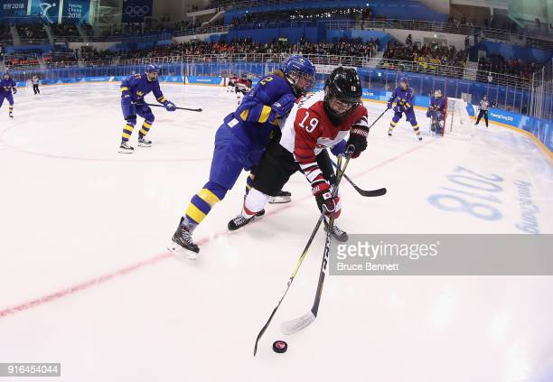 Emmy Alasalmi of Sweden and Miho Shishiuchi of Japan battle for the puck in the second period during the Women's Ice Hockey Preliminary Round Group B...