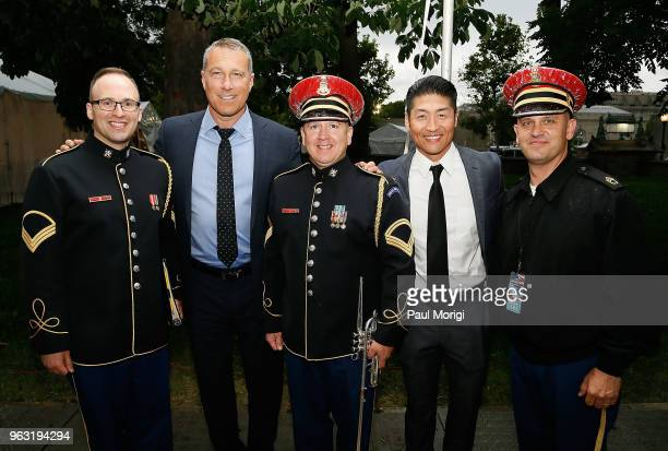 Emmy Golden Globe and SAG Awardnominated actor John Corbett and Star of Chicago Med Brian Tee pose for a photo with Army servicemen backstage at the...