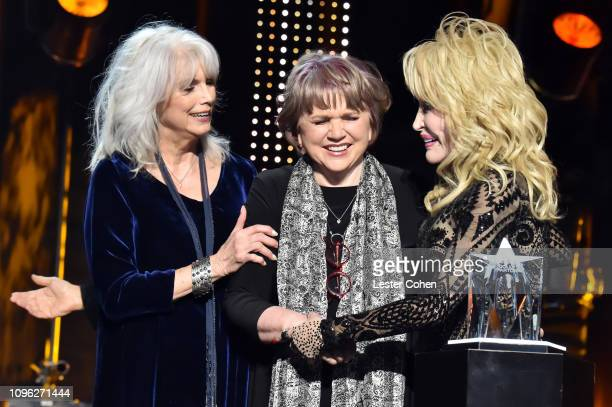 Emmylou Harris and Linda Ronstadt present the MusiCares Person of the Year award to Dolly Parton onstage during MusiCares Person of the Year honoring...