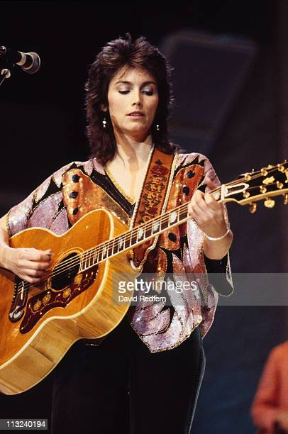 Emmylou Harris, U.S. Singer-songwriter and musician, playing guitar during a live concert performance, 1984.
