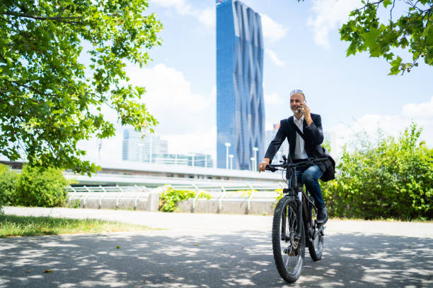 e-mobility commute to work businessman on electric bicycle - city manager stock pictures, royalty-free photos & images