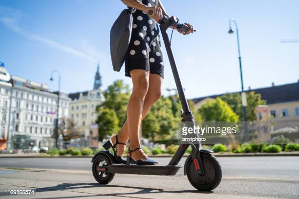 e-mobility commute to work, businesswoman on electric push scooter in city - electric scooter stock pictures, royalty-free photos & images