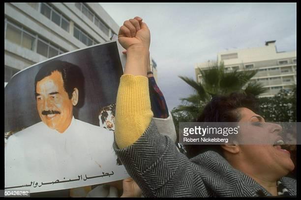 Emoting fist-raising woman amid pro-Iraqi demonstrators w. Pres. Saddam Hussein's portrait, in gulf war protest outside US Embassy.