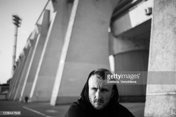 emotional black and white portrait of a sitting on asphalt at stadium young man in black hood, who looks away the camera with strong, confident look - atmospheric mood stock pictures, royalty-free photos & images