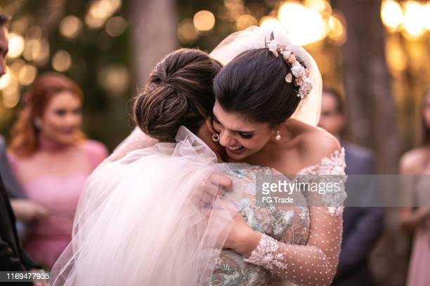 emotional bride being congratulated by her mother - bridesmaid stock pictures, royalty-free photos & images