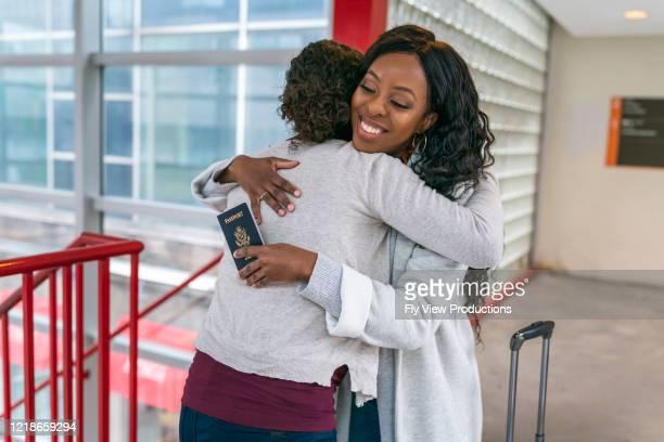 amigos emocionados se abraçando antes da mulher sair em viagem internacional - amizade feminina - fotografias e filmes do acervo