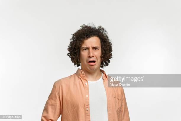 emotional portrait of a curly guy with brown hair - öffentlicher auftritt stock-fotos und bilder