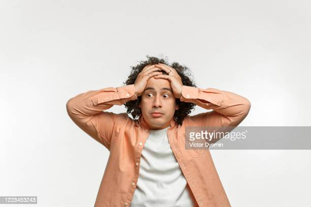 emotional portrait of a curly guy with brown hair - blame stock pictures, royalty-free photos & images