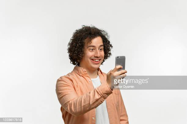 emotional portrait of a curly guy with brown hair - 手に持つ ストックフォトと画像