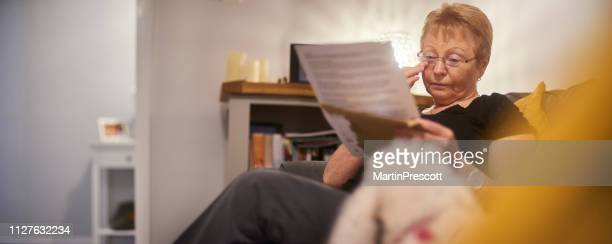 emotional senior woman crying as she reads letter - grandma invoice stock pictures, royalty-free photos & images