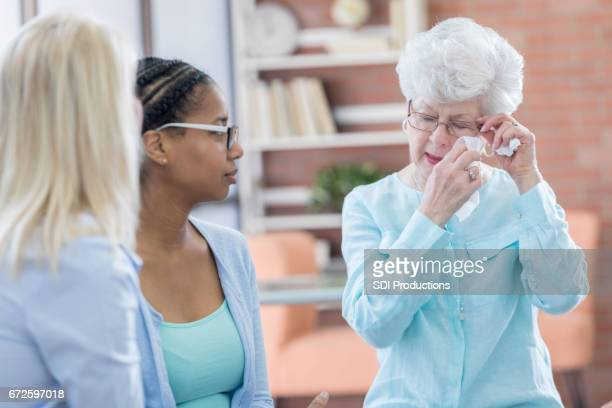 Emotional senior woman discusses something in therapy session