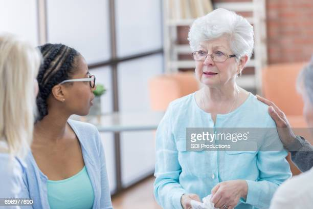Emotional senior woman during group therapy session