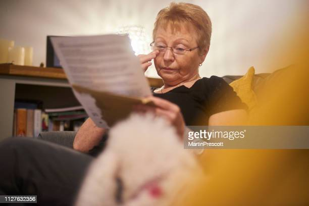 emotional senior woman reading letter - message stock pictures, royalty-free photos & images