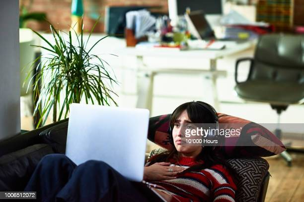 emotional young woman using laptop and looking upset - regarder attentivement photos et images de collection