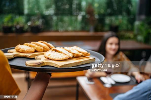empanadas being delivered to customers in buenos aires cafe - empanada stock pictures, royalty-free photos & images