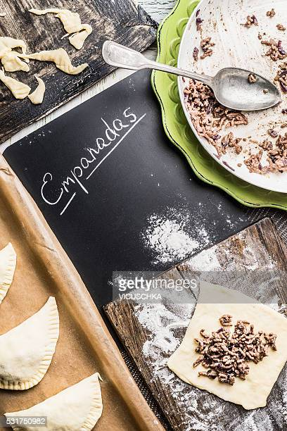 Empanadas preparation on kitchen table with chalkboard and text